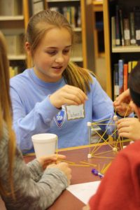 Middle School female works on a STEM project with classmates.