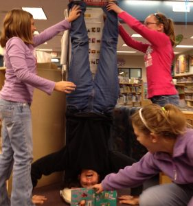 Mrs. Adair, Horizon librarian, reading a children's book while standing on her head, with the help of three students.