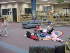 Elementary students reading on the library dragon rug