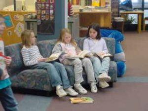 Three elementary girls reading on a couch in the library