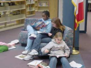 Three elementary students reading on a couch in the library