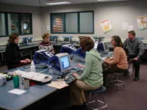 Teachers working on computers in the library computer lab