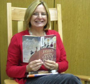 Mrs. Tegels sitting in a wooden chair reading James and the Giant Peach.
