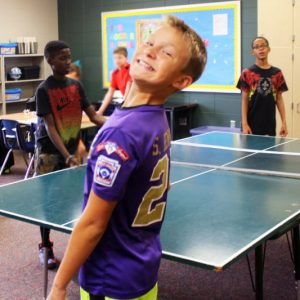 Summit student plays ping pong with friends during SAS.