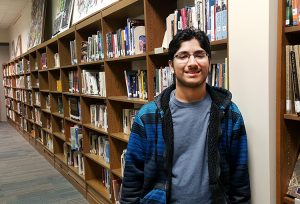 JHS student Afshan Chandani stands in front of library books.