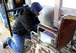 A school bus driver secures a wheelchair on the bus.
