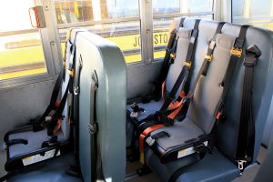 Photo of bus seats equipped with harnesses and seat belts.