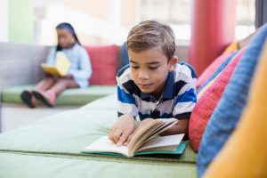 schoolboy lying on sofa and reading book in library