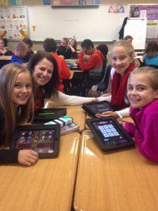 Summit teacher Nancy Ellis works with three female students to get their ipads set up.