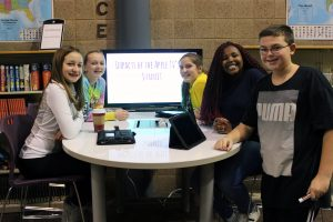 Five middle school students stand around a white board table smiling