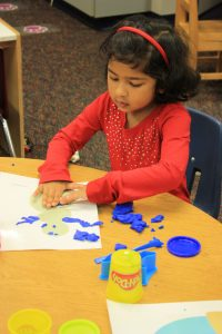 A preschooler plays with play dough during class