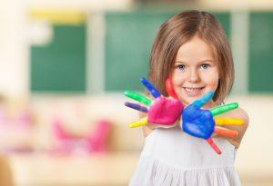 Preschool student showing her painted fingers