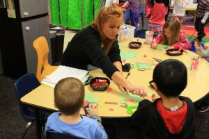 Photo of a Johnston preschool classroom with a teacher helping students.