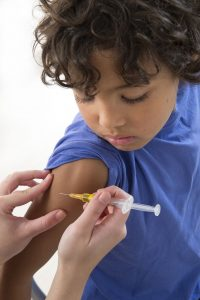 33719608 little boy looking at his arm, while receiving vaccine