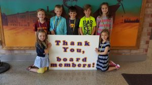 """Lawson students gather around a """"Thank you board Members"""" sign for school board appreciation month."""