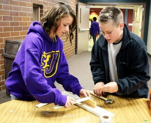 Summit seventh graders Rachael (left) and Conner (right) work together to build a simple machine representing interaction between literary characters.