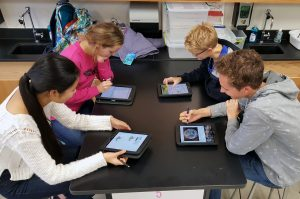 Four students sitting at a science table using ipads and talking.
