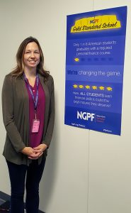 JHS teacher Kayla Bousum stands next to the NGPF poster
