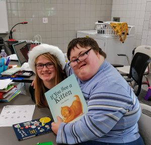 Two Johnston high School students smile after opening a present and receiving a new book.
