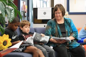 two young boys and a teacher sit together and read