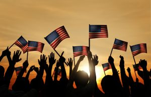 34537582 group of people waving american flags in back lit